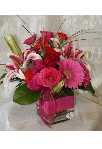 """Hot Pink Chic Stargazer and Pink Rose Bouquet from Enchanted Florist- Brilliantly bright reds and pinks are arranged in a chic square cube. Hot pink roses, red roses, star gazer lilies, pink gerbera daisies with a fiery spout of bear grass are arranged in a clear cube with a pink treatment. Approximately 12""""W x 12""""H   SKU RM129"""