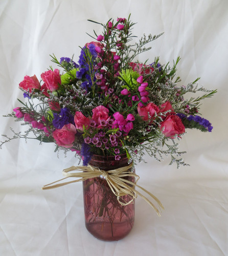 """Wildflower Garden in Mason Jar from Enchanted Florist - A beautiful mixture of wild flowers and hot pink spray roses in a pin mason jar. A spring time staple! Professionally designed in a mason jar, this spring bouquet includes pink spray roses, green poms, wax flowers, heather, statice and is adorned with a raffia bow. Approximately 14""""H x 11""""W  For local delivery only. SKU RM143"""