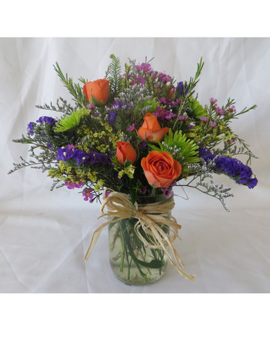 """Wildflower Bliss in Mason Jar from Enchanted Florist - A wildflower bouquet is a great spring time flower bouquet perfect for a country girl or garden lover. This wildflower bouquet includes seasonal flowers found in your garden along with orange spray roses and green button poms. This small bouquet makes a great thank you gift and is only available during the spring time. Approximately 10""""H x 8""""W   SKU RM145"""