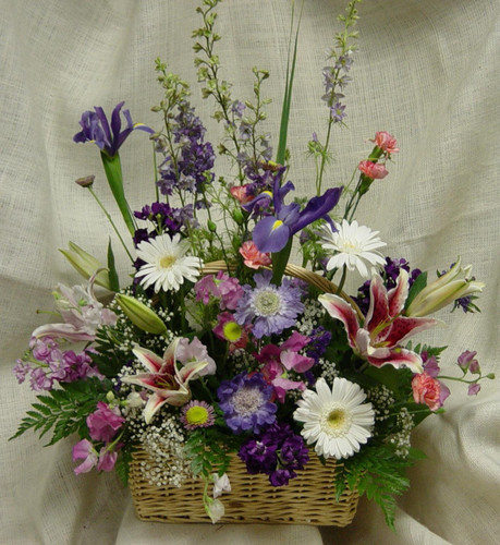 """Spring Garden Funeral Basket by Enchanted Florist - This lovely spring garden basket for a funeral is full of spring flowers and is appropriate for the sympathy service or family home. Spring time flowers include iris, white gerbera daisies, stargazer lilies, lavender larkspur, baby's breath and more to complete a cheerful basket of flowers. Approximately 24"""" W x 30"""" H SKU RM503"""