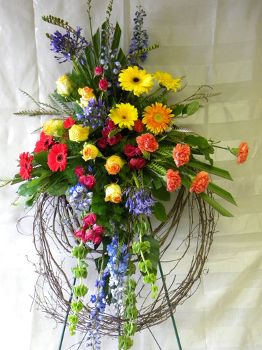 "Eternal Sunshine Grapevine Sympathy Wreath from Enchanted Florist - This bright and colorful floral grapevine wreath will express your compassion to all in attendance. Our funeral wreath includes bright yellow roses, red gerbera daisies, blue delphinium, and more. A unique funeral option for a dearly loved family member.  Approximately 32""W x 54""H SKU RM510"