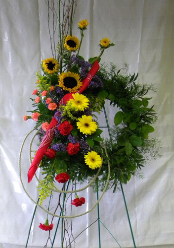 Texas Pride Cowboy Funeral Wreath Flowers from Enchanted Florist - a floral wreath covered in beautiful colorful flowers including happy sunflowers and a red bandanna. Sympathy flowers delivered to local funeral homes in Houston TX and Pasadena TX  RM511