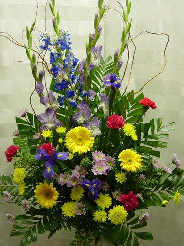 Spring Time Funeral Flower Arrangement by Enchanted Florist Pasadena TX - a lush funeral arrangement of purple gladiolas, blue delphinium, yellow gerbera daisies, and hot pink carnations. Can be delivered same day or next day to most Funeral Homes in Clear Lake TX and Houston TX. RM512