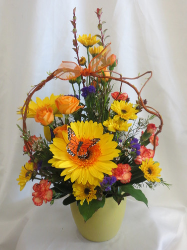"Sunshine Melody Yellow and Orange Bouquet by Enchanted Florist Pasadena TX. A fun bright flower arrangement with yellow flowers and orange flowers in a cute ceramic pot with a curly willow arch. Includes gerberas, spray roses, viking poms and mini carnations. Approximately 18""H x 10""W  For local delivery only.  SKU RM159"