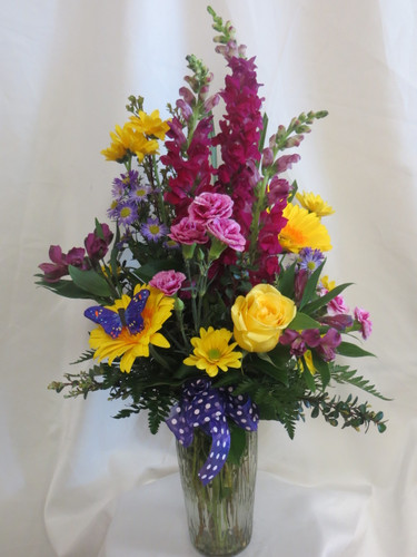 Purple People Pleaser Flower Bouquet with Yellow Roses and Gerberas by Enchanted Florist Pasadena TX. Bright yellows and pleasing purple flowers in a clear glass vase. Flowers include purples and yellow roses and purple carnations. RM162
