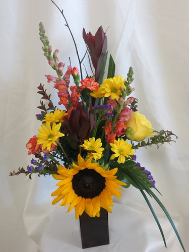 Fancy Free Sunflower Rose Bouquet by Enchanted Florist Pasadena TX. A pretty mixed flower vase arrangement that includes sunflowers, snapdragons, yellow roses, and more in a dark colored vase. RM164