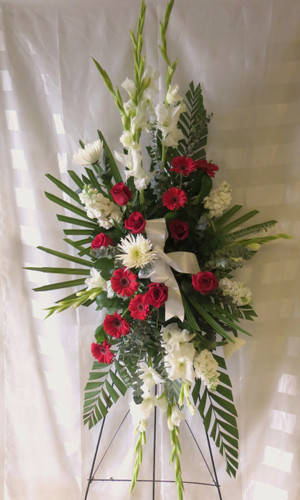 """Starry Night Red Standing Spray Funeral Flowers by Enchanted Florist Pasadena TX. A beautiful a classic combination of red roses, white gladiolas, red gerbera daisies, white spider flowers and white stock together in a standing funeral spray of flowers for a funeral visitation and funeral service. Sympathy flowers that are sure to stand out, just like your loved one, one last time. Approx 70"""" H x 30"""" W.  (size does not include stand)   SKU RM518"""
