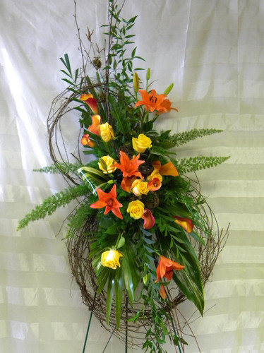 "Autumn Harvest Grapevine Funeral Flower Wreath by Enchanted Florist TX. Send unique and creative funeral flowers with this grapevine flower wreath standing spray. A custom creation by our talented designers. Sympathy flowers include orange lilies, yellow roses, and orange mini calla lilies with tropical foliages arranged on this grapevine wreath. Approximately 70""H x 28""W. (size does not include stand)  SKU RM519"