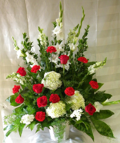 "Sweet Devotions Red and White Funeral Flowers by Enchanted Florist Pasadena TX. Send a sweet sympathy flower arrangement of traditional red carnations, classic red roses, white gladiolas, white snapdragons, and white hydrangeas in a white funeral container.  Approximately 34""H x 26""W (size does not include easel)  SKU RM520"