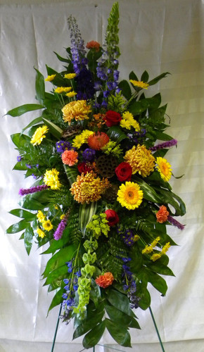 """Bronze Memory Masculine Fall Sympathy Standing Spray by Enchanted Florist Pasadena TX. This lovely masculine sympathy spray of fall themes flowers includes football mums, protea, bells of Ireland, delphinium, red roses and so much more. Approx 56""""H x 26""""W (size does not include stand)  SKU RM527"""