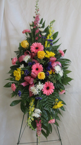 Beautiful Farewell Pink Sympathy Spray of Flowers by Enchanted Florist Pasadena TX.  A mixed color spray of sympathy flowers in a standing spray and includes pink gerbera daises, yellow roses, pink larkspur and yellow snapdragons. Cheap funeral flowers. RM539