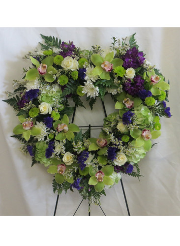 With All My Heart Shaped Funeral Wreath Flowers by Enchanted Florist Pasadena TX. Heart shaped funeral wreath of sympathy flowers including green cymbidium orchids, white roses, green hydrangeas, white cushions, and purple stock. Heart shaped funeral flowers. RM540