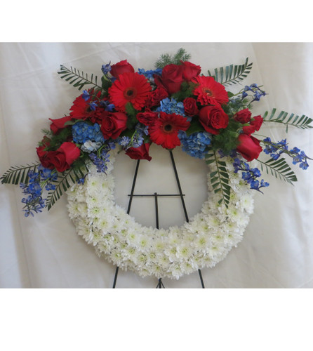 "Stars and Stripes Patriotic Funeral Wreath Flowers by Enchanted Florist. Sympathy flowers include red roses, red gerberas daisies, blue hydrangeas and blue delphinium (similar to blue bonnets). Send a patriotic sympathy flower wreath delivery today to most Houston and Pasadena funeral homes. Approximately 23""H x 30""W (does not include stand size) SKU RM542"