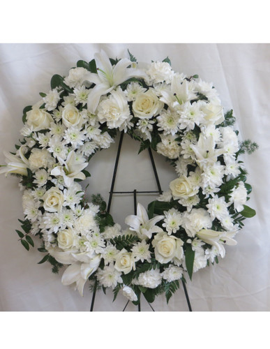 "Sincere Serenity White Funeral Wreath Spray by Enchanted Florist Pasadena TX. An all white sympathy flower funeral wreath full of white lilies, white roses, white carnations, and white cushions. All white funeral flowers is a classic combination for any sympathy service. Standard and Deluxe are approximately 22""H x 22""W   SKU RM543"