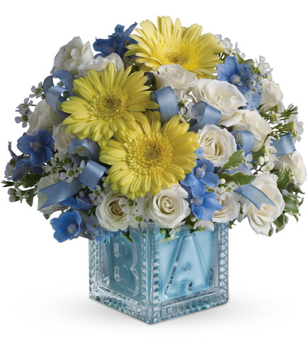 New Baby Boys First Crystal Block with Flowers by Enchanted Florist Pasadena TX. Baby's first building block is complete with a lovely assortment of delicate flowers to welcome any new baby boy in to the world. Includes yellow gerbera daisies, white spray roses and the blue flowers are delphinium.  RM307