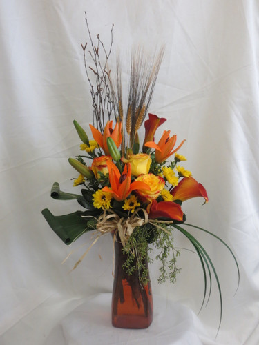 Autumn Excellence Yellow Rose Flower Bouquet by Enchanted Florist Pasadena TX. A beautiful fall bouquet of flowers and includes orange lilies, yellow roses, orange mini calla lilies, and yellow Vikings accented with branches, wheat, leaves and grasses. The bouquet comes expertly designed in a orange vase with a raffia bow.  RM235