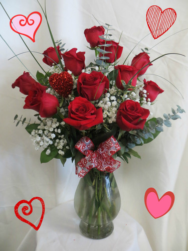 "Our Most Popular Dozen Red Roses for Valentines Day by Enchanted Florist Pasadena TX. This is our most popular and best value for Valentines Day for one dozen red roses. The freshest premium red roses will be hand designed in our upgraded Bella vase, with popular baby's breath, upgraded premium greenery, a Valentines Day bow and a romantic heart to show your love. Approximately 18""W x 22""H  SKU RM921"