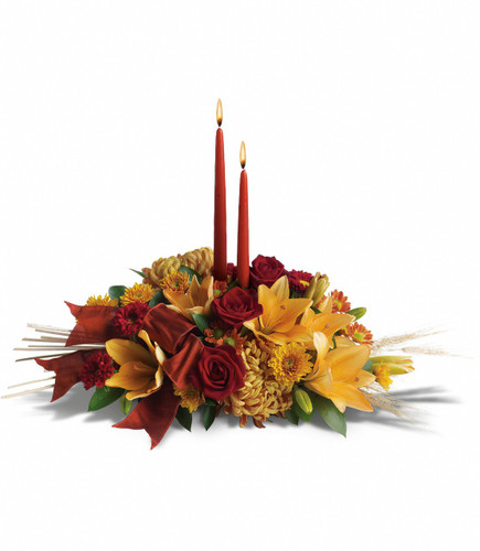 "Graceful Glow Thanksgiving Centerpiece from Enchanted Florist TX. Delightful red roses, orange asiatic lilies, orange and bronze chrysanthemums, and burgundy ribbon surround two elegant taper candles. Accents of natural wheat make this gift wildly festive! Approximately 22""W x 17""H   SKU RM226"