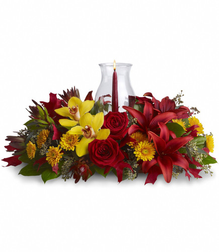 "Glow of Gratitude Centerpiece from Enchanted Florist Pasadena TX. Brilliant yellow cymbidium orchids, red roses, burgundy asiatic lilies, bronze cushions, red leucadendron, eucalyptus and red oak leaves, are on dazzling display - surrounding an artisan candle and hurricane glass. A glowing way of showing gratitude. Approximately 22""W x 12""H   SKU RM232"