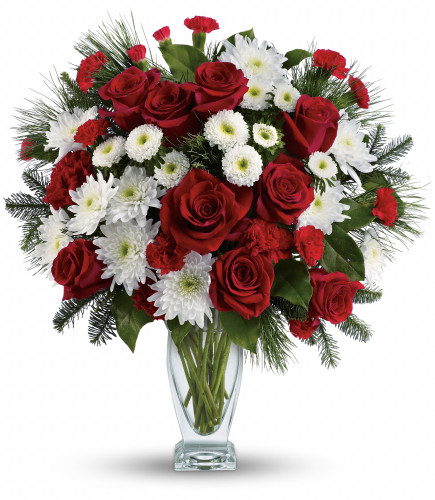 """Winter Kisses Christmas Bouquet from Enchanted Florist Pasadena TX. Our heartwarming bouquet includes red roses, red carnations, red miniature carnations, white cushions, noble fir, white pine and lemon leaf. Delivered in a gorgeous glass Couture vase. Approximately 15"""" W x 17"""" H.   SKU RM252"""