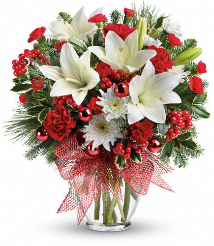 """Merry All The Way White Lily Christmas Bouquet from Enchanted Florist. White oriental lilies, red carnations, red miniature carnations and white cushions is accented with noble fir, white pine and red berries. Finished with a festive red ribbon and delivered in a glass vase. Approximately 15"""" W x 17"""" H   SKU RM259"""