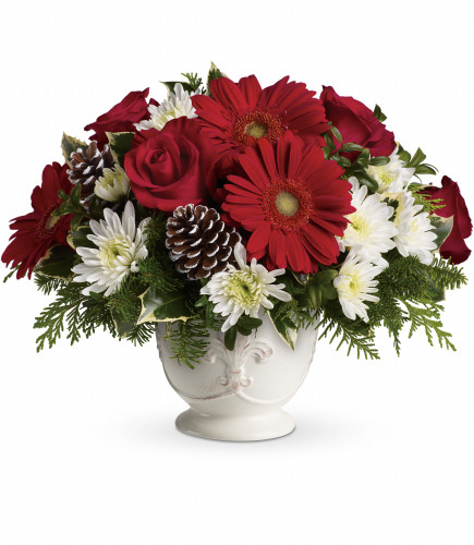 """Simply Merry Christmas Centerpiece from Enchanted Florist. Red gerberas, red roses and white cushion spray chrysanthemums are accented with tips of flat cedar, noble fir, holly and assorted greens. Delivered in Teleflora's French country pot. Approximately 15"""" W x 12"""" H   SKU RM254"""