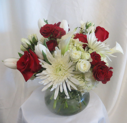 Knock Out Flower Bouquet by Enchanted Florist Pasadena TX. This lush and contemporary bouquet is artfully designed in our large Rosie Posie vase with all white flowers of calla lilies, hydrangeas, tulips, spiders, and spray roses and then accented with baby and large red roses to deliver that pop of color. A premium bouquet! Daily delivery to Friendswood. RM155