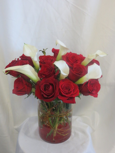 "Forever Love Red Rose Flower Bouquet by Enchanted Florist Pasadena TX. She will run to your embrace after having these stunning flowers delivered to her home or office. This luscious bouquet arrives in a contemporary cylinder vase accented with red rocks and is filled with 15 red roses and white miniature calla lilies.  Approximate size is 15""H x 13""W  For local delivery only.   SKU RM146"