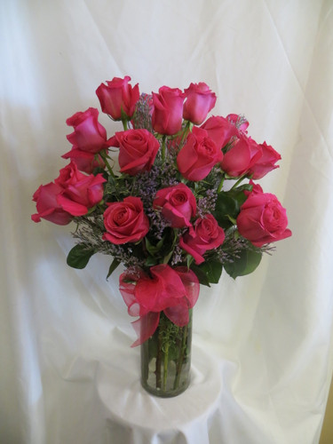 Oh So HOT Pink 2 Dozen Roses by Enchanted Florist Pasadena TX.  Romantic bouquet of lush hot pink roses arranged in a contemporary cylinder vase and accented with purple filler limonium. RM369