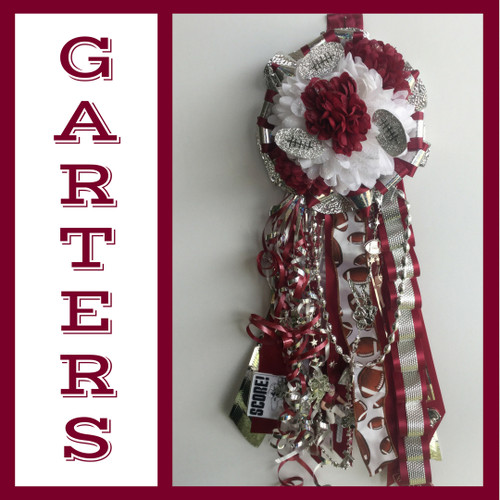 The Maroon and White Homecoming Garter from Enchanted Florist includes a single garter flower, trinkets, metallic chain, the Loopty braid, and garter band in the school colors of your choice. This color is perfect for Pearland High School and Clear Creek High School. HMC141