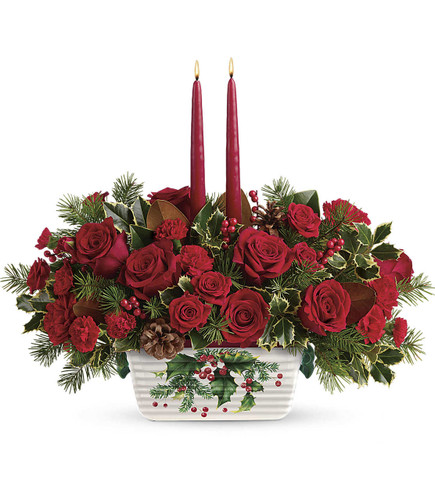 Holly Glow Centerpiece by Teleflora This festive centerpiece features red roses, red spray roses, red carnations, red miniature carnations, douglas fir, variegated holly, and magnolia leaves. Delivered in Teleflora's Halls Of Holly dish.  T18X105B