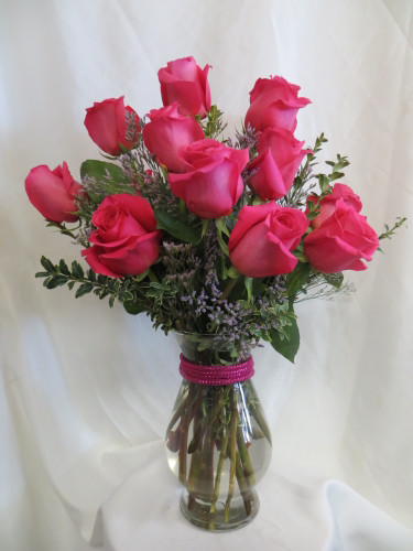 "HOT Momma One Dozen Hot Pink Roses by Enchanted Florist Pasadena TX - One dozen long stems hot pink roses are arranged in a vase with purple limonium and ribbons as pictured. Don't make you special someone design her own flowers from a box! Our beautiful Ecuadorean roses are hand designed by expert floral artisans.  One dozen roses is approximately 18""W x 22""H   SKU RM373"