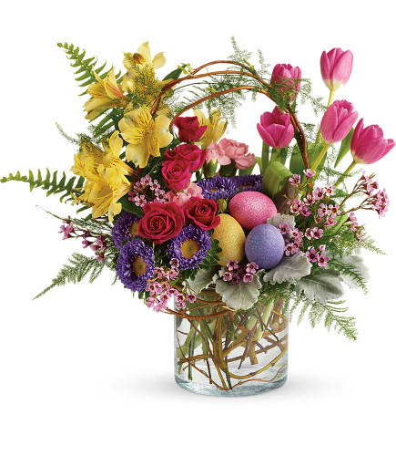 "Pop of Easter Flowers for Spring from Enchanted Florist. This delightful bouquet includes pink roses, pink tulips, yellow alstroemeria, pink miniature carnations, lavender matsumoto asters, lavender wax flower, dusty miller, asparagus plumosus, sword fern, pitta negra, and curly willow. Delivered in a clear cylinder vase. Approximately 18 1/2"" W x 15"" H SKU RM130"