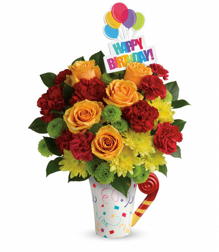 Fun Happy Birthday Roses Mug Bouquet from Enchanted Florist. Your birthday bouquet includes orange roses, red carnations, green buttons and yellow cushions that are arranged with greenery and hand delivered in our exclusive Cheers to You mug. SKU 179