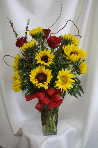 Sunshine Sunflower and Red Rose Arrangement from Enchanted Florist. Sunflowers are easily one of most popular flower and are paired here with classic red roses for a beautiful bouquet sure to excite any sunflower lover. It is accented with various greens, curly willow, and a lady bug for a hidden surprise. Houston flower delivery. SKU RM184