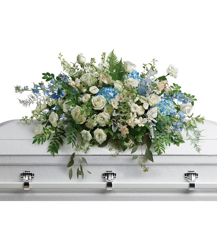 Blue and White Casket Spray of Roses and Flowers from Enchanted Florist. A stunning casket spray includes blue hydrangea, white roses, white spray roses, white alstroemeria, white lisianthus, blue delphinium, white larkspur, white stock, white waxflower, and additional various greenery and filler flowers for a beautiful look. SKU RM571