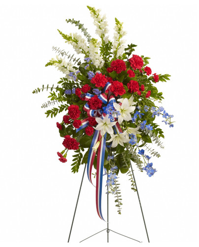 Red White and Blue Funeral Flowers Standing Spray by Enchanted Florist Pasadena TX. This gorgeous selection of flowers such as white lilies and snapdragons, blue delphinium, red carnations and miniature carnations, eucalyptus and more create this all-American spray. SKU RM572
