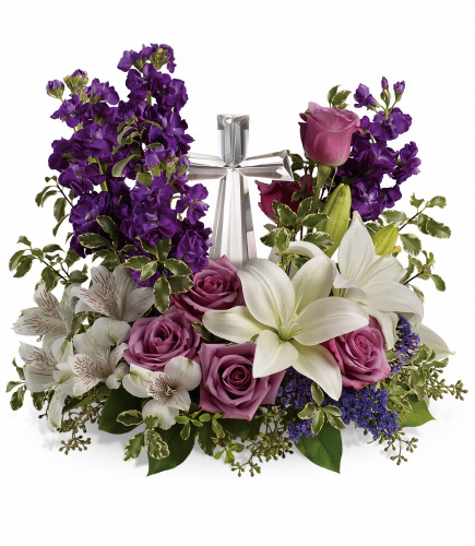 "Majestic Purple Large Crystal Cross from Enchanted Florist. This funeral bouquet of flowers includes lavender roses, white oriental lilies, white alstroemeria, purple stock and purple seafoam statice and is then arranged with fresh greeneries. It includes the large crystal cross keepsake. Cross is approximately 11""H x 6""W x 2""D. Sympathy flower arrangement is approximately 15"" W x 17"" H SKU RM577"