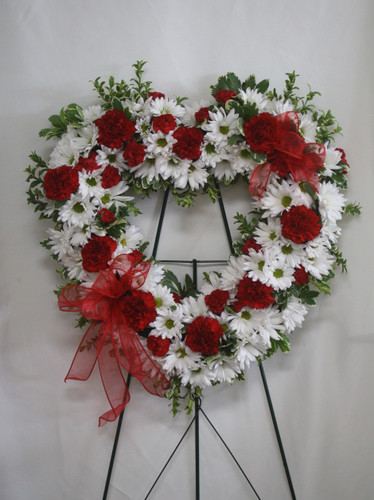 Red and White Heart Shaped Funeral Flowers from Enchanted Florist. This red and white heart shaped wreath of flowers includes red carnations and mini pixie carnations white white daisies and is accented with various greenery foliages and red sheer ribbon. SKU RM506