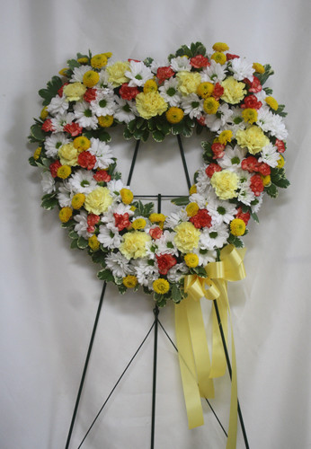 "Yellow, Orange, and White Heart Shaped Funeral Flowers from Enchanted Florist. A beautiful heart shaped funeral flower spray made of yellow carnations, orange mini carnations, and white daisies. Arrives on a sympathy easel stand. Approximately 22""H x 22""W (Size does not include stand) SKU RM516"