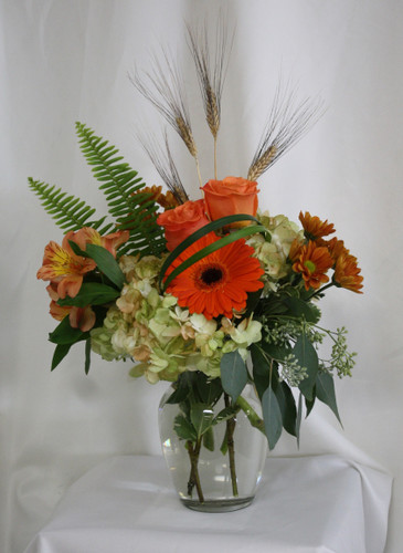 "Autumn Dew Drops Bouquet in Orange from Enchanted Florist. Your beautiful fall bouquet will arrive in a clear vase and includes hydrangeas, orange roses, orange gerbera daisies, alstromeria and butterscotch daisies and is accented with sword fern and wheat grass. Approximately 13""W x 17""H SKU RM212"