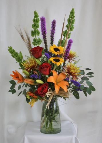 "Fantastically Fall Red Rose Bouquet from Enchanted Florist. Your fall arrangement includes orange Asiatic lilies, sunflowers, red roses, purple liatris, bronze spiders, bells of Ireland and assorted greenery for a fall floral bouquet to enjoy. Approximately 18""W x 30""H SKU RM214"