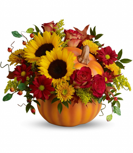 """Pretty Pumpkin Sunflower Fall Arrangement by Enchanted Florist. The radiant bouquet includes red roses, yellow sunflowers, yellow cushions, red daisies, solidago, huckleberry and oak leaves. Approximately 15"""" W x 13"""" H  SKU RM220"""
