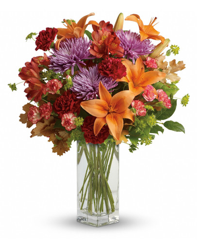 "Fall Brightens Orange Lily Bouquet from Enchanted Florist. Our lovely bouquet includes orange asiatic lilies, orange alstroemeria, red carnations, orange miniature carnations, lavender disbud chrysanthemums, bupleurum, lemon leaf and fall oak leaves. It arrived hand delivered in a beautiful clear bunch vase.  Approximately 18"" W x 21"" H SKU RM222"