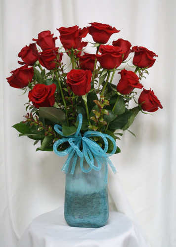 "Turquoise Vase with Red Rose Bouquet from Enchanted Florist. This beautiful bouquet of roses includes 15 premium red roses arranged along side red huck and adorned with a turquoise bow and arrives in our beautiful exclusive turquoise art vase. Approximately 24""H x 16""W SKU RM356"