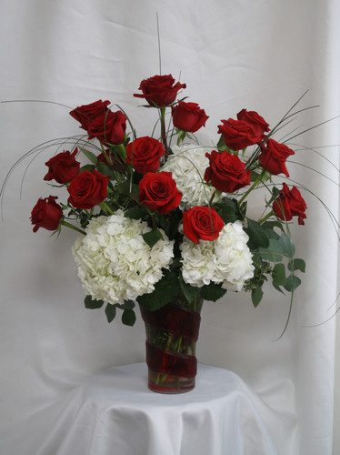 "Red Swirl White Hydrangea and Red Rose Bouquet from Enchanted Florist. Our one of a kind bouquet includes the Red Swirl keepsake vase and has 15 beautiful Ecuadorian red roses designed in it alongside white hydrangeas, bear grass and eucalyptus to accent this arrangement perfectly. Approximately 24""H x 16""W SKU RM358"