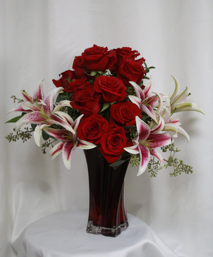 "Luxurious Love Red Rose and Stargazer Bouquet from Enchanted Florist. Our one of a kind bouquet includes the Red Luxurious keepsake vase and has 15 beautiful Ecuadorian red roses designed in it alongside fragrant stargazer lilies and seeded eucalyptus to accent this arrangement perfectly. Approximately 19""H x 13""W SKU RM359"