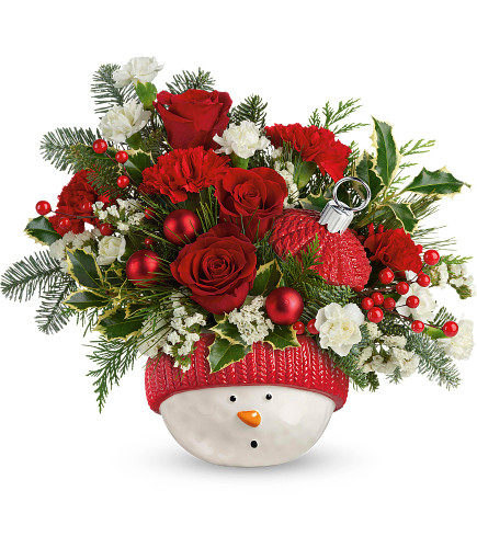 """Snowman Ornament with Red Carnations Bouquet from Enchanted Florist. Red carnations, miniature red carnations, white sinuata statice and variegated holly are accented with noble fir, flat cedar, and white pine. Delivered in Teleflora's Snowman Ornament. Approximately 14"""" W x 12"""" H SKU T12X400"""