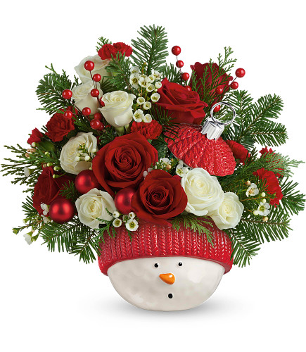 "Winter Fun Snowman Ornament with White Roses Bouquet from Enchanted Florist. Festive red roses, mini white spray roses, miniature red carnations, and white wax flower are accented with noble fir and cedar. Delivered in Teleflora's Snowman Ornament keepsake. Approximately 14"" W x 13"" H SKU T20X405"