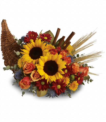 """Classic Sunflower Cornucopia Centerpiece from Enchanted Florist. Dazzling yellow sunflowers, light orange roses and spray roses, red daisies, yellow cushions, eucalyptus, magnolia leaves, cinnamon sticks and wheat are perfectly arranged in a wicker cornucopia. Approximately 19"""" W x 15"""" H SKU RM228"""